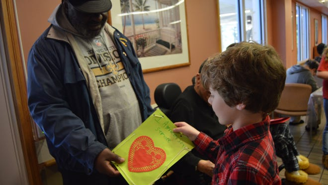 "Jacob Miller, a fourth-grader at Pollock Elementary school, gives his handmade ""thank you"" card to a veteran at Alexandria VA's community living center."