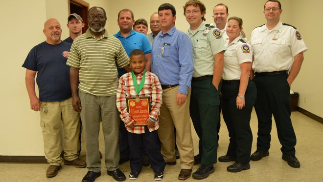 Trinton Jacobs, 6, was honored after his 911 call helped to save his grandfather, John Drummer. Jacobs is pictured with his grandfather and members of Bunkie Fire Department and Acadian Ambulance Services.