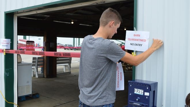 In this Thursday, July 13, 2017 photo, Clinton County Junior Fair Board member Ridge Beam places quarantine signs on the hog barn at the Clinton County Fairgrounds in Wilmington, Ohio. State officials have ordered the slaughter of nearly 300 hogs at at the county fair in southwest Ohio after at least two animals tested positive for swine flu.