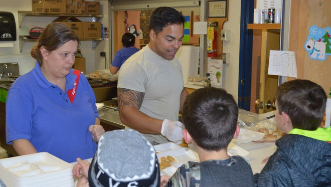 Students at Wilson Elementary School line up to get lunch from a member of the Air Force.