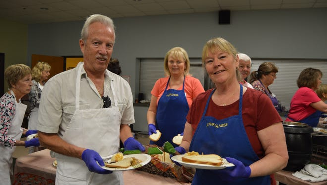 Larry Kraatz, left, Marlene Wingate, and Colleen Audette smile as they get ready to serve Thanksgiving dinner at the First Church of God, Vero Beach.