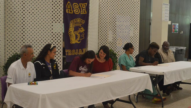 With their familes watching, ASH's Brianna Serret (third from left) and Daniel Lewis (second from right) sign with Centenary College for swimming Wednesday.