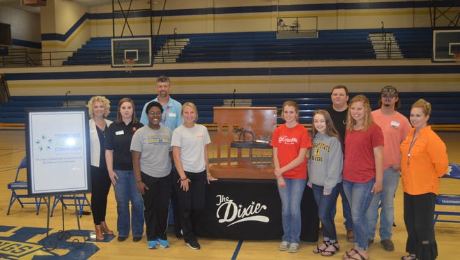 Huntingdon students Tia Compton, Ryleigh Bailey, Maggie Guess, Alexys Stephens, and Jordan Cole pose for a picture after their designs were announced as the finalists for the new sign at The Dixie. Also pictured are Lori Nolen from The Dixie, Margaret Szopinski, mechanical engineer at Granges, David Earley, welding instructor at TCAT, TCAT welding students Peyton Lindsey and Dusty Smith, and Dana Wyatt, art instructor for Huntingdon High.