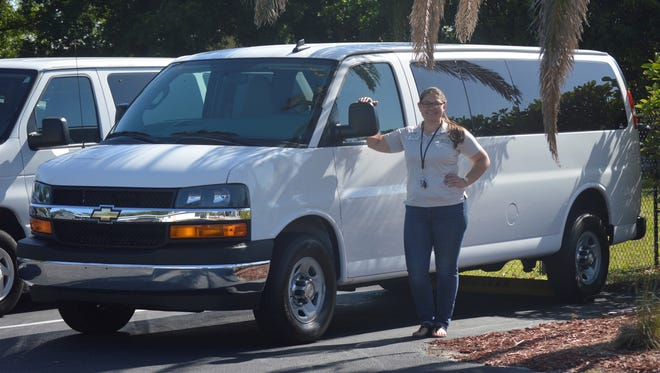 The Hope for Families Center Children's Enrichment Specialist Maggie Harding inspects the new van, funded through the John's Island Community Foundation.