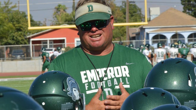 Longtime Dinuba High head football coach Kevin Scharton speaks to his players after a practice on Aug. 3 in Dinuba.