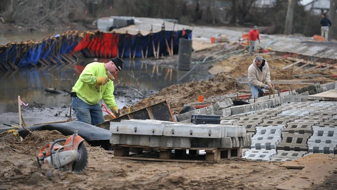 Schiavone Construction worker Samuel Barnes, of Millville (left), places concrete formwork molds, part of the work on Burnt Mill Pond dam, Wednesday, Feb. 17 in Vineland.
