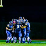 Members of the DeWitt offense celebrate after JD Ross ran for a touchdown to put DeWitt up 20-0 over St. Johns early in the 2nd quarter of their game Friday October 9, 2015 in DeWitt.  DeWitt claimed the CAAC Red title with a 49-21 win.