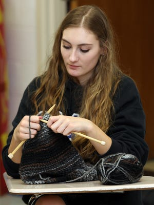 Sarah Krems knits a scarf that was donated to Scarf it Up for Those in Need in 2012.