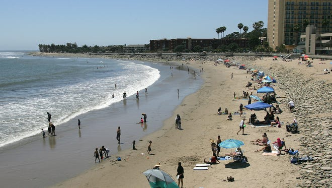 In this file photo, people enjoy warm weather at the beach near the Ventura Pier. A heat wave that arrived Monday will peak Tuesday, with temperatures staying warm until Saturday.