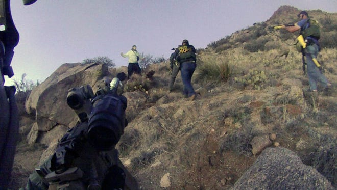 This March 16, 2014 photo of an Albuquerque Police Department lapel camera still, shows a standoff with James Boyd, 38, before firing six shots at the man. Lawyers for two Albuquerque police officers say both will face charges in the March killing of Boyd a homeless camper, a shooting that generated sometimes violent protests around the city and sparked a federal investigation.