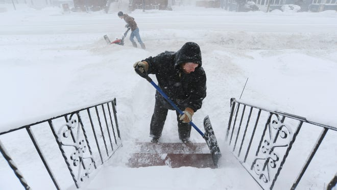 Jared Downing, front, and Drew Maier, back, with King Chop, L.L.C., a landscape and lawn care service based in Stevensville, Mich., clear snow from a residence along Niles Avenue in St. Joseph, Mich.