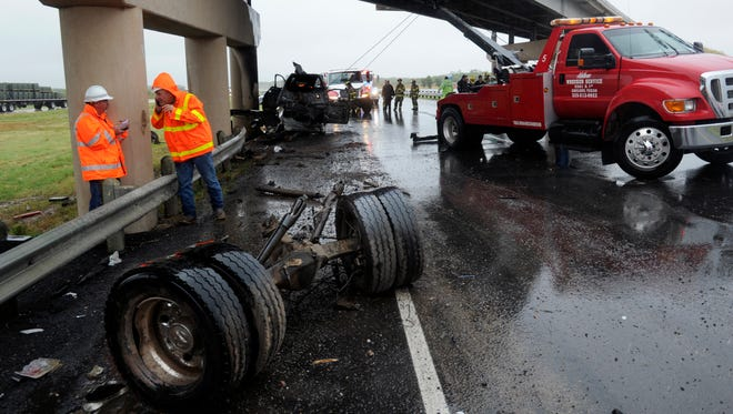 Crews work to clear the remnants of a pickup that burst into flames after colliding with the Business 20 overpass on the westbound side of Interstate 20 in Tye Tuesday Sept. 26, 2017.