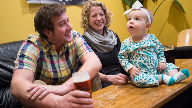 Chris and Melanie Wood, along with 8-month-old Charlotte, attend a gathering of Pints and Parents at Horse and Dragon Brewing Company Wednesday, January 20, 2015. The group of new mothers and fathers meets at area breweries
