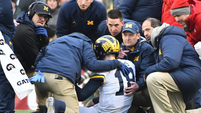 Michigan head coach Jim Harbaugh and members of the medical staff gather around injured quarterback Brandon Peters in the third quarter.