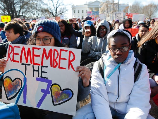 Students sit in silence as they rally in front of the White House in Washington, Wednesday, March 14, 2018.