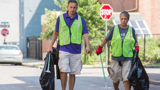 Jim Cira, left, the driver of the Jobs Van, and Lori Gilbert pick up trash as part of a new program to reduce panhandling on Wednesday, July 11, 2018, in Over-the-Rhine.