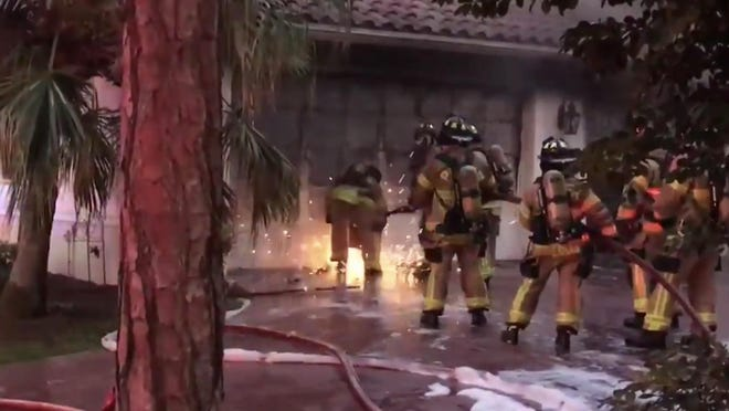 Sparks fly from tools used by firefighters to breach a garage door and gain access to a fire in a Wellington home on Jan. 11, 2020. Still image taken from video on Palm Beach County Fire Rescue Twitter account.