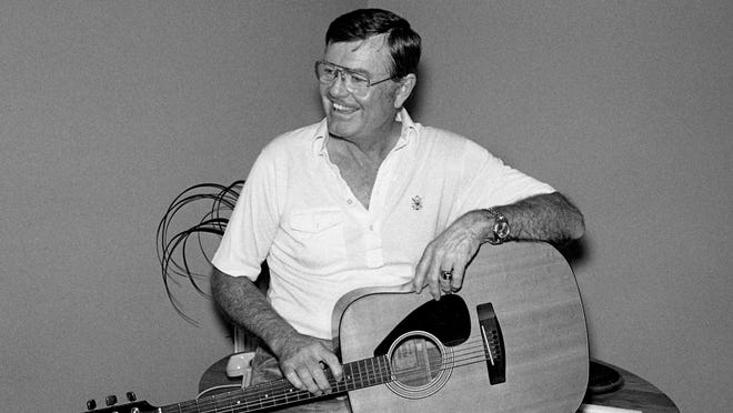 University of Texas athletic director and former head coach Darrell Royal relaxes with a guitar at the offices of Tree Publishing Co. Feb. 23, 1979. Royal is in town for a visit to the Nashville Songwriters Award banquet.