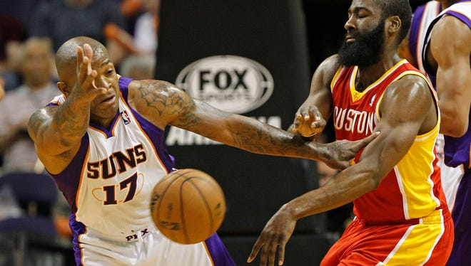 Suns shooting guard P.J. Tucker (left) tries to block a pass by Rockets shooting guard James Harden during the first half of their game on Monday, April 15, 2013 in Phoenix.