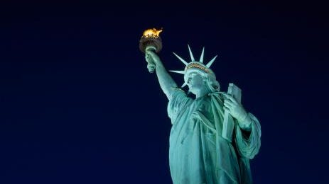 Low angle view of Statue of Liberty lit up at night in New York.
