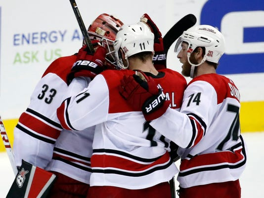 Carolina Hurricanes goalie Scott Darling (33), center Jordan Staal (11), and defenseman Jaccob Slavin (74) celebrate after an NHL hockey game against the Washington Capitals, Thursday, Jan. 11, 2018, in Washington. (AP Photo/Alex Brandon)