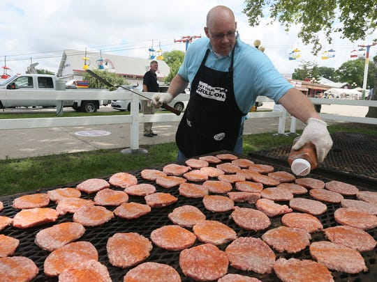 Calvin Vandekrol of Polk City helps flip pork burgers for the Tama County Pork Producers during the World Pork Expo at The Iowa State Fairgrounds Wednesday, June 4, 2014.