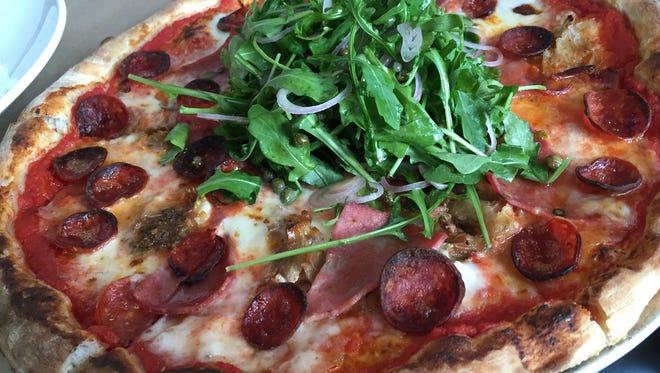 Housemade porchetta, mortadella and pepperoni share pizza space with a salad featuring Eden Farms arugula.