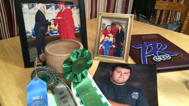 Photos of Marcus Weaver, 19, sit along with his career passport from Pickaway-Ross Career and Technology Center and a wooden mug he made in 2013 at his parents home near Kingston. Weaver was killed Saturday when a truck crashed into Arby's on North Bridge Street.
