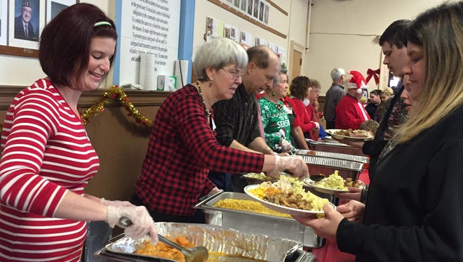 Volunteers serve food on Christmas Day during the annual Bandera holiday dinner at the American Legion in Binghamton.