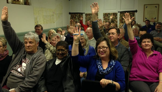 Supporters of Historic Onancock School raise their hands to signify their willingness to volunteer to help Friends of Onancock School at a town hall meeting on Monday, Feb. 8, 2016.