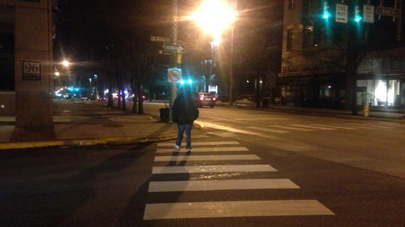 Sergio Rosario, in crosswalk, crosses King Street on South George Street in York after using what change he could acquire from strangers to buy a burger at McDonald's.
