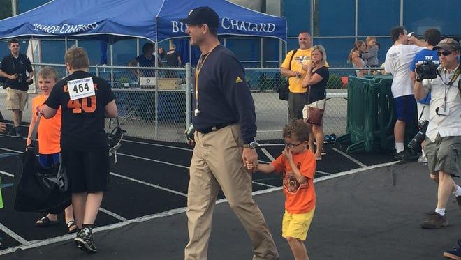 Michigan football coach Jim Harbaugh walks with his son Jack at a satellite camp June 1, 2016, at Indianapolis Bishop Chatard High School.