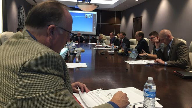 Dr. Mark Lynn, left, and other members of the University of Louisville Foundation board reviewed documents during an annual meeting Thursday.