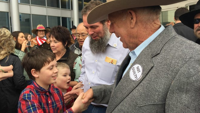 Amid a crunch of supporters, Cliven Bundy shakes the hands of children outside the Federal Court House in Las Vegas after his release from custody Jan. 8, 2018.