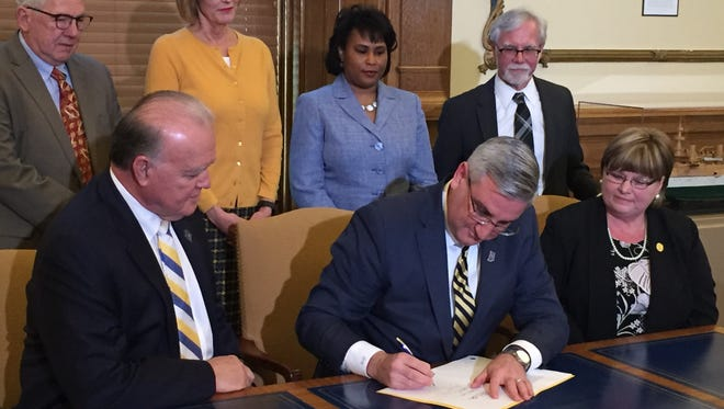 Gov. Eric Holcomb signs into law a measure requiring sexual harassment training for state lawmakers.