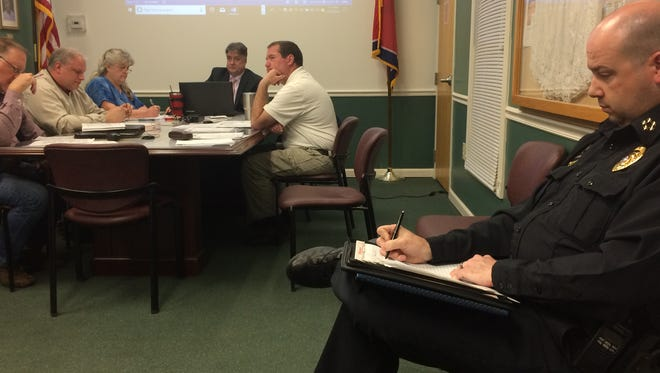 Coopertown Police Chief Lawrence Dennis takes notes while the Board of Mayor and Alderman convenes during its regular meeting March 27, 2018.
