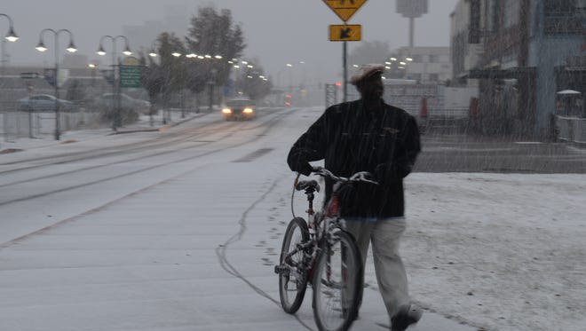 A man walks his bicycle in the snow earlier this month near downtown Reno.