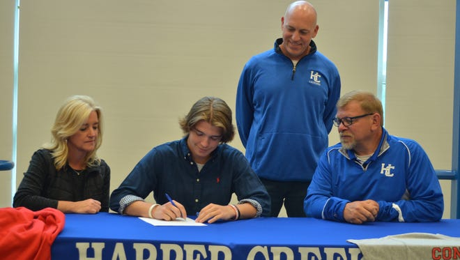 Harper Creek's Jordan Robinson has signed to play lacrosse at Concordia University. He is joined by his parents, Jim Robinson and Kathy Robnson and Harper Creek Coach Flesch.