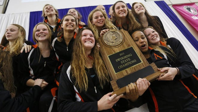 Members of the Ames swim team hold their first place team trophy  Saturday, Nov. 7, 2015, during the state girls' swimming meet in Marshalltown.