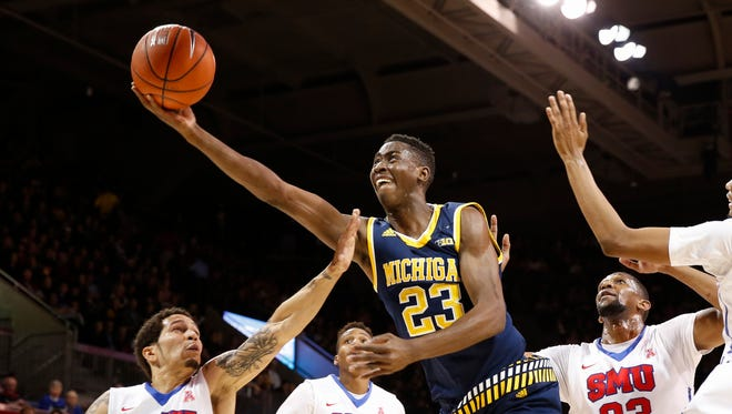 In this Dec. 8, 2015, file photo, Michigan guard Caris LeVert (23) shoots the ball in front of SMU guard Nic Moore (11) and guard Jarrey Foster (10) during the first half of an NCAA basketball gamein Dallas.