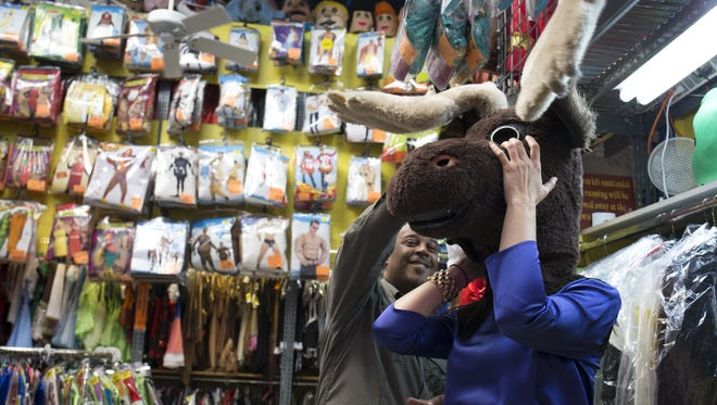 Dennis Bullock helps his co-worker, Stephnie Sinclair, try on a Halloween costume at Easley's Fun Shop in 2014.