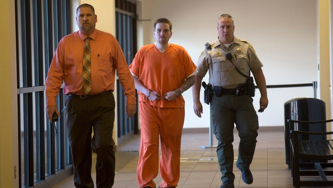 Timothy Serrano is escorted into court for a sentencing hearing on Oct. 31 at Aztec District Court on a second-degree murder conviction. Serrano now faces a new charge for auto burglary.