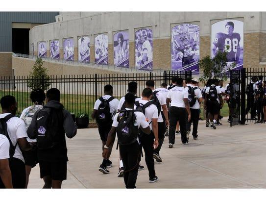 The Abilene Christian University football team walk
