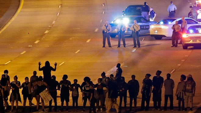 In this Sept. 22, 2016 photo, police confront protesters blocking Interstate-277 during demonstrations following the police shooting of Keith Lamont Scott, in Charlotte, N.C. Emotionally wrenching politics, foreign conflicts and shootings at home took a toll on Americans in 2016, but they are entering 2017 on an optimistic note, according to a new poll that found that a majority believes things are going to get better for the country next year.