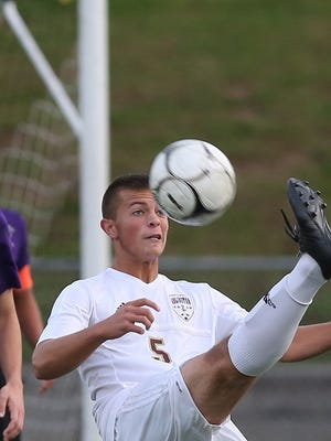Arlington's Eric Layden, right, passes over New Rochelle's Ethan Monley during the boys soccer Section 1 Class AA championship game at Lakeland High School in Shrub Oak Oct. 29, 2016. New Rochelle won the game 3-0.