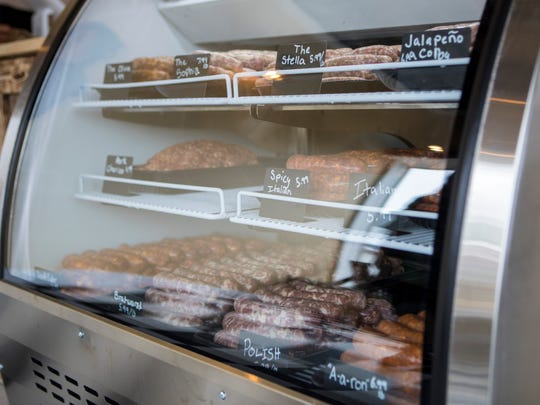 Trays of different handmade sausages are displayed for customers to browse and buy by the pound. More offerings are on the way.