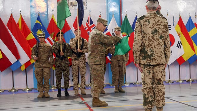 Commander of the International Security Assistance Force (ISAF), Gen. John Campbell, center, cases the ISAF flag during a ceremony at  ISAF headquarters in Kabul, Afghanistan, on Sunday.