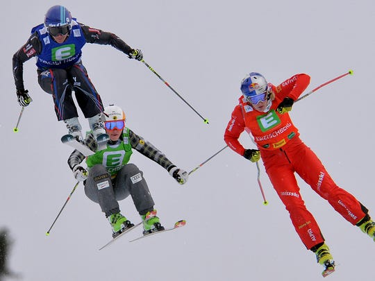 Winner Ophelie David of France, left, second placed Fanny Smith, right,  of Switzerland and third placed Marielle Thompson of Canada speed down the track during the final race of the women's Ski  Cross  World Cup  in Kreischberg, Austria, on Jan. 25. 2014.