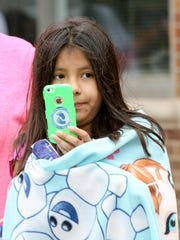 Xochilt Rosas, 10, keeps warm in her blanket as she records the Memorial Day Parade in Dover on May 29, 2017. Alexandra Pais/ The Daily Record