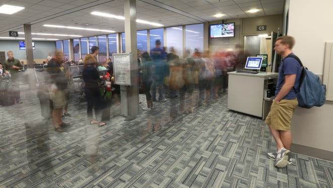 Passengers board a morning flight at the Des Moines airport July 1.